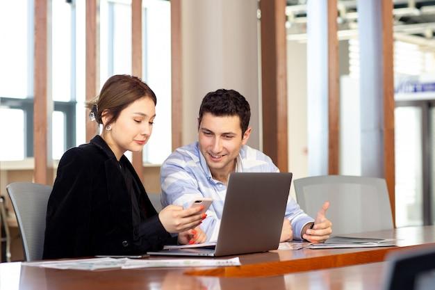 彼女のオフィス仕事の仕事の建物の中で何かを見て電話を見て若い男と一緒に黒いシャツの黒いジャケットの正面の若い美しい女性実業家