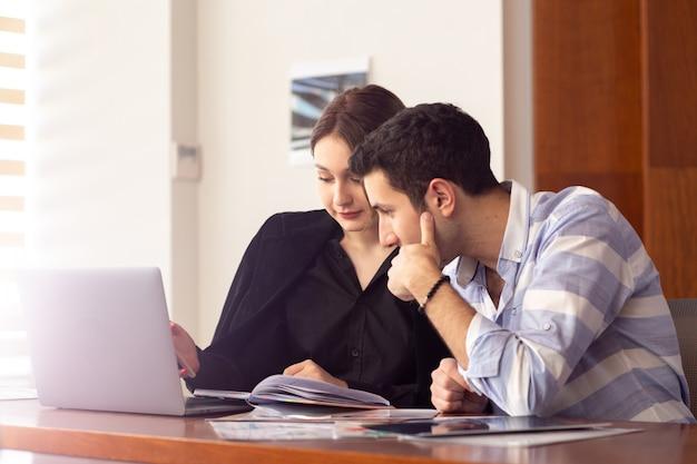 正面の若い美しい女性実業家と彼女の銀のラップトップを使用して彼女のオフィスの仕事の建物内の問題を議論する若い男と一緒に黒いシャツの黒いジャケット