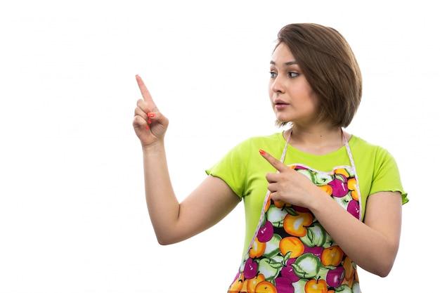 Вид спереди молодая красивая домохозяйка в зеленой рубашке красочный мыс выражение пальцами на белом фоне дом женщина кухня