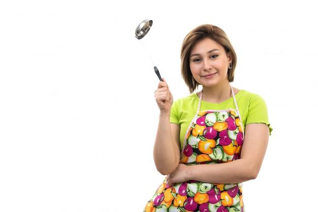 Вид спереди молодая красивая домохозяйка в зеленой рубашке красочной накидке держит большую серебряную ложку, улыбаясь на белом фоне уборка дома кухня