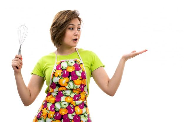 白い背景の家のクリーニングキッチンにキッチンアプライアンスを保持している緑のシャツカラフルなケープの正面の若い美しい主婦