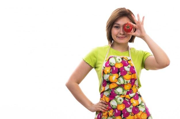 白い背景の家の掃除のキッチンで笑顔の赤いトマトを保持している緑のシャツのカラフルなケープの正面の若い美しい主婦