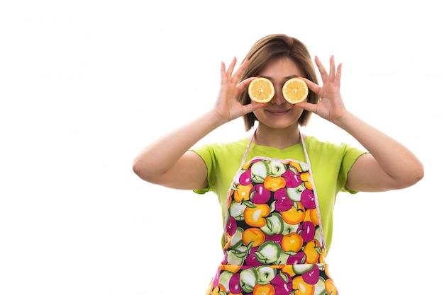 Вид спереди молодая красивая домохозяйка в зеленой рубашке красочный плащ держит нарезанный апельсин, улыбаясь на белом фоне уборка дома кухня