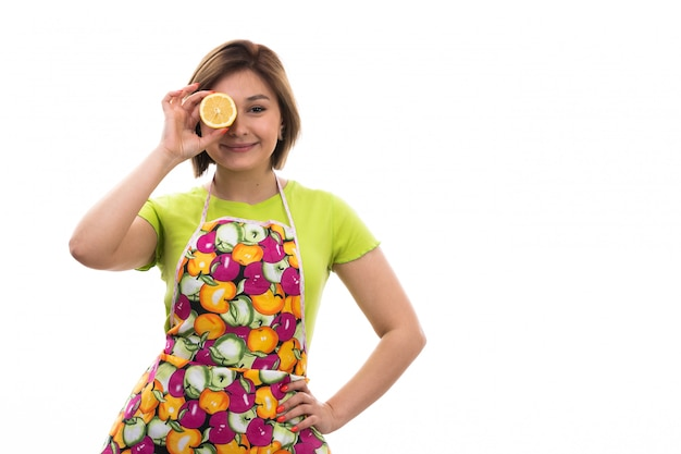 緑のシャツのカラフルなケープを保持している正面の若い美しい主婦スライスオレンジホワイトバックグラウンドハウスクリーニングキッチンに笑みを浮かべて