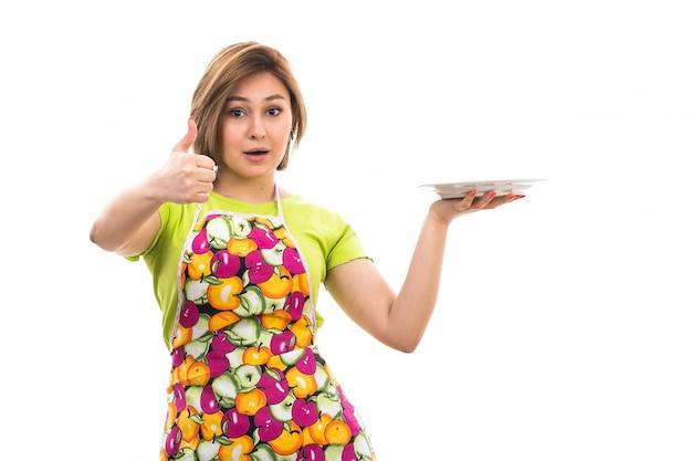 緑のシャツのカラフルなケープの白い背景の家のクリーニングキッチンに笑みを浮かべて白いプレートを保持している正面の若い美しい主婦