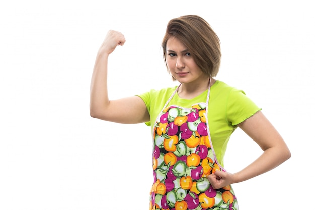 白い背景の家の女性のキッチンで屈曲ポーズグリーンシャツカラフルなケープの正面の若い美しい主婦