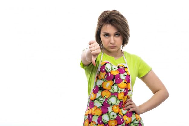 白い背景の家の女性のキッチンに大きな兆候を示さない緑のシャツのカラフルなケープの正面の若い美しい主婦