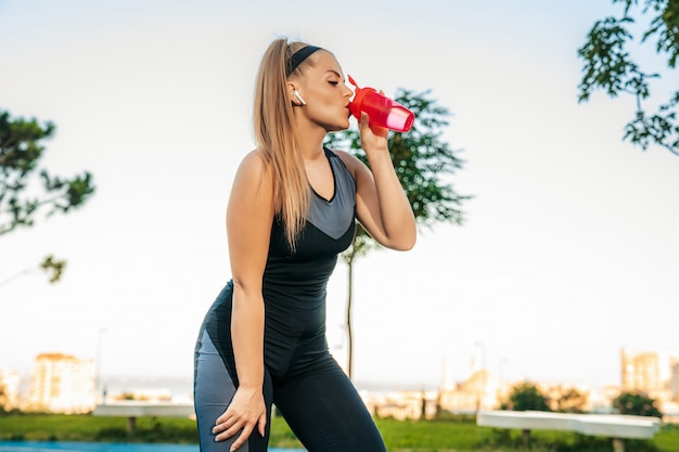 水のボトルと屋外ジムに立っている女性