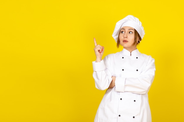 若い女性の白いクックスーツと白い帽子の思考のポーズで調理