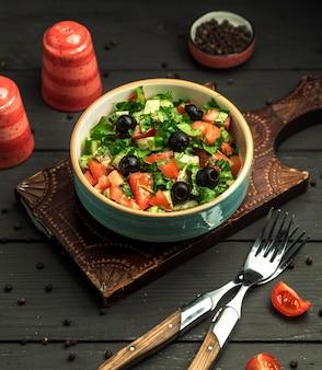 Чаша греческого салата с оливками, огурцами, помидорами и зеленью
