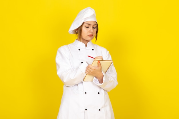 若い女性の白いクックスーツとメモを書く白い帽子で調理