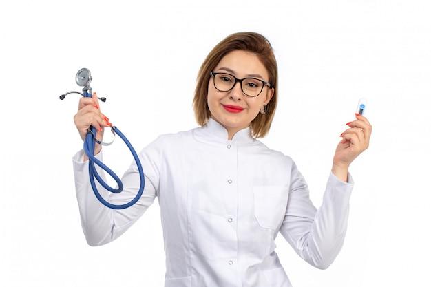 温度測定と笑みを浮かべて聴診器を保持している白い医療スーツの若い女性医師