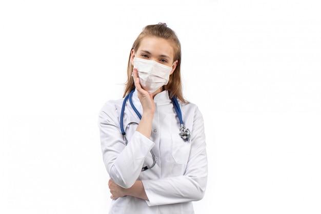 白の白い防護マスク聴診器思考ポーズで白い医療スーツの若い女性医師