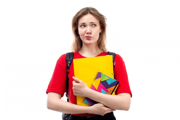 白のコピーブックファイルを保持している赤いシャツ黒バッグの正面の若い女子学生