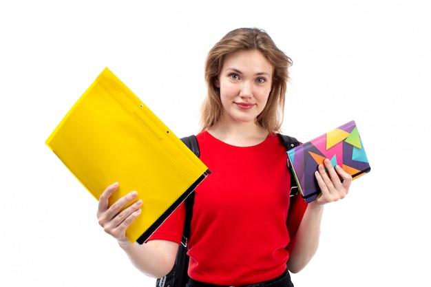 白に笑みを浮かべてコピーブックファイルを保持している赤いシャツ黒バッグの正面の若い女子学生