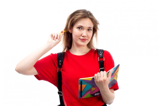 コピーブックファイルを保持している赤いシャツの黒いバッグの正面の若い女性学生は白で書き留めて笑顔