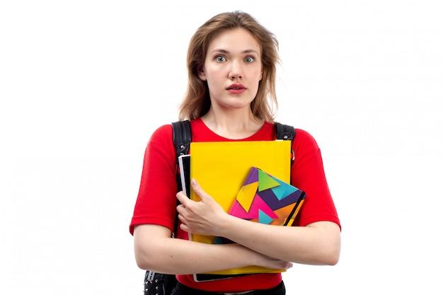 コピーブックを保持している赤いシャツの黒いバッグの正面の若い女子学生は白の表現に衝撃を与えた