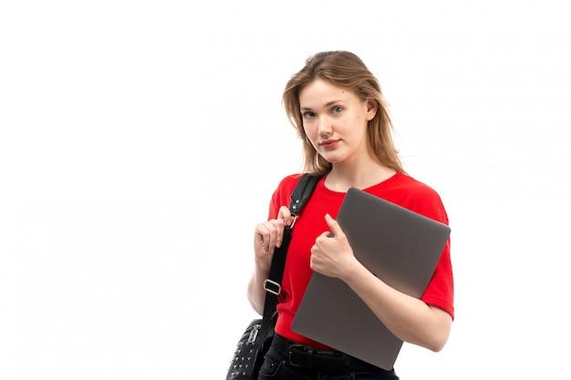 白のファイルを保持している赤いシャツ黒バッグの正面の若い女子学生