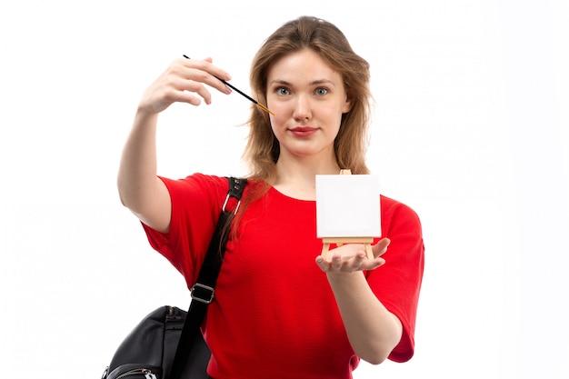 白に笑みを浮かべて絵筆絵を保持している赤いシャツ黒バッグの正面の若い女子学生
