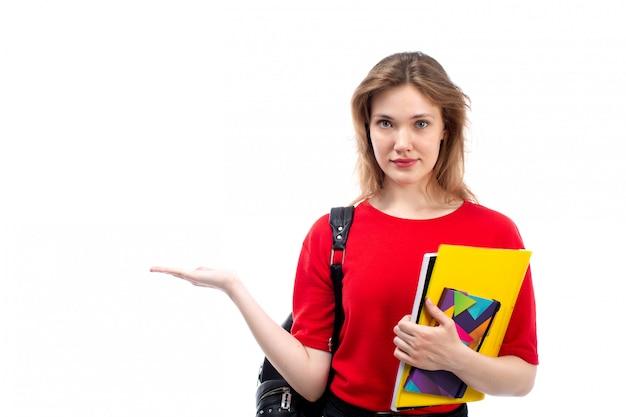 白のペンとコピーブックを保持している赤いシャツ黒バッグの正面の若い女子学生
