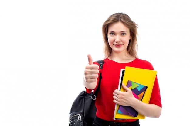 ペンとコピーブックを白に笑みを浮かべて保持している赤いシャツ黒バッグの正面の若い女子学生