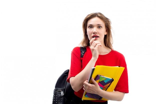 白で驚いたペンとコピーブックを保持している赤いシャツ黒バッグの正面の若い女子学生