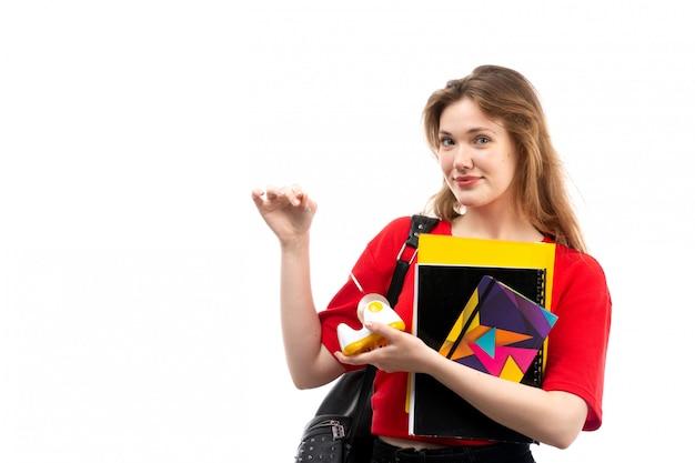白地にコピーブックを保持笑みを浮かべて赤いシャツ黒バッグの正面の若い女子学生