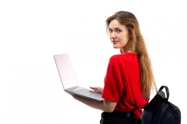 Вид спереди молодая студентка в красной рубашке черная сумка, используя ноутбук на белом