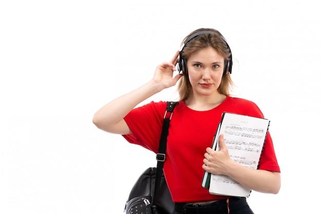 白のコピーブックを保持している黒のイヤホンと赤いシャツ黒バッグの正面の若い女子学生
