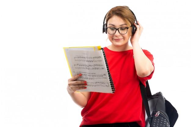 Вид спереди молодая студентка в красной футболке черные джинсы слушает музыку через черные наушники, читая заметки на белом