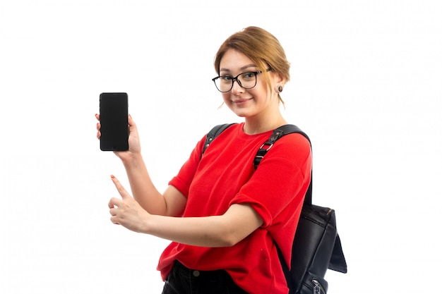 Вид спереди молодая студентка в красной футболке в черной сумке держит черный смартфон, улыбаясь на белом