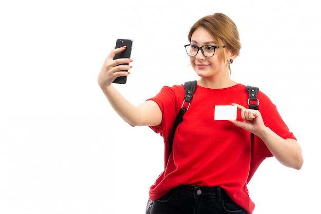 Вид спереди молодая студентка в красной футболке в черной сумке держит черный смартфон, принимая селфи, улыбаясь на белом