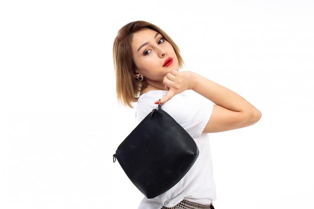 白いシャツと白に黒い小さな袋を保持している光のモダンなズボンの正面の若い女性