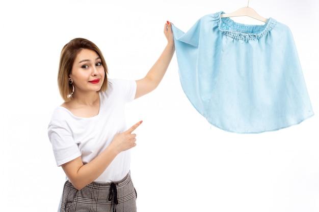 白いシャツと白に青いスカートを保持している光のモダンなズボンの正面の若い女性