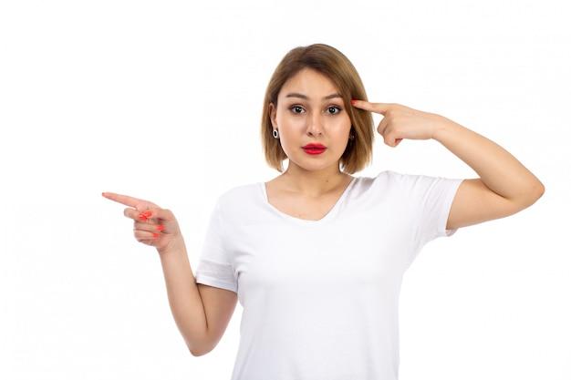 白の思考をポーズ白いシャツの正面の若い女性