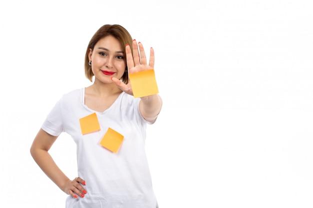 白に笑みを浮かべてポーズオレンジ色のノートと白いシャツの正面の若い女性