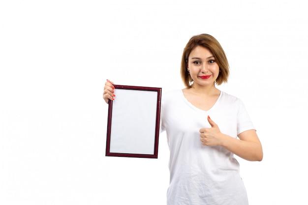 Вид спереди молодая дама в белой футболке держит бордовый фоторамка, улыбаясь на белом