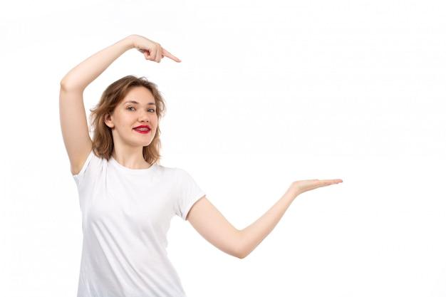 Вид спереди молодая дама в белой футболке позирует счастливой улыбкой на белом
