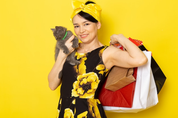 Вид спереди молодой леди в желто-черном цветочном платье с желтой повязкой на голове, держащей пакеты с покупками и котенка на желтом