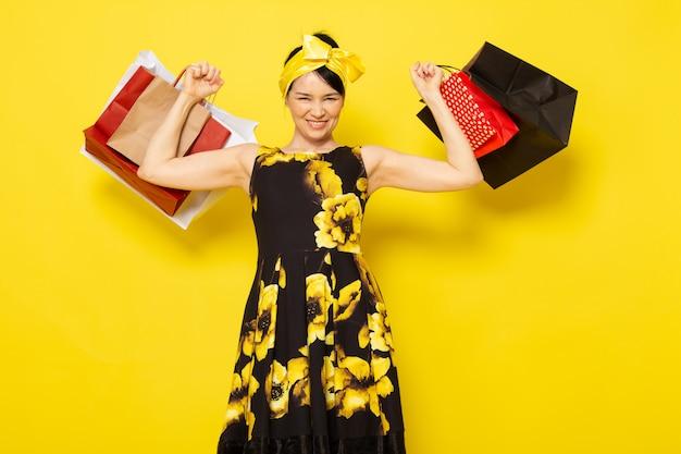 黄色に笑みを浮かべてショッピングパッケージを保持している頭の上に黄色の包帯でドレスをデザインした黄黒花の正面の若い女性