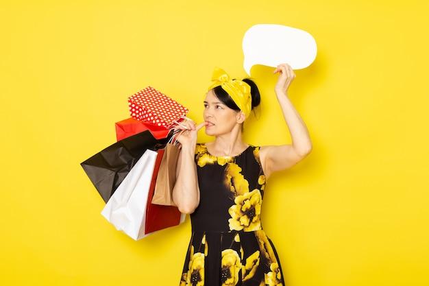 黄色の黒い花の正面図の若い女性は黄色のショッピングパッケージ白い看板を保持している頭の上の黄色の包帯でドレスを設計しました