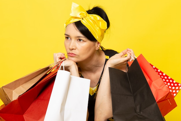 黄色の黒い花の正面の若い女性が黄色のショッピングパッケージを保持していると考えて頭に黄色の包帯でデザインされたドレス