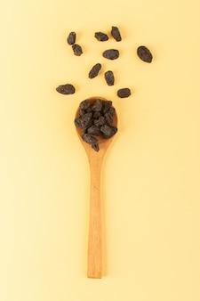 茶色の木のスプーンの中のトップビューブラックドライフルーツはクリーム色の上面を分離