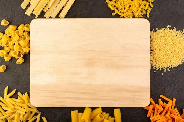 暗い上に分離されたさまざまな形成された黄色の生パスタと共に木製の茶色の机の上から見る
