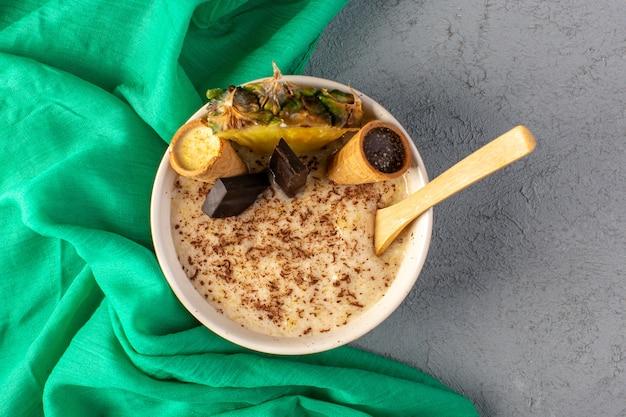 トップビューチョコデザートブラウンパイナップルスライスチョコバーアイスクリームグレーの緑のティッシュと一緒に白いプレート内