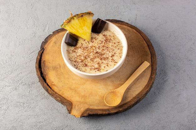 Шоколадный десерт сверху шоколадно-коричневый с ломтиками ананаса на коричневом деревянном столе и серый