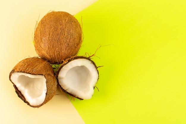 Вид сверху целых кокосовых орехов и молочной свежей спелой массы, на кремово-фисташковом цвете