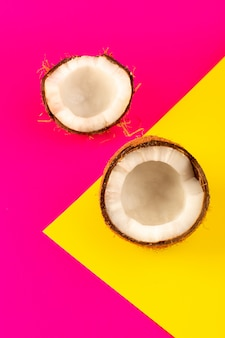 Вид сверху нарезанные кокосовые орехи и целая молочная свежая спелая, изолированные на розовый и желтый