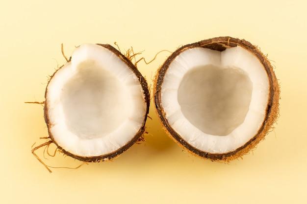 トップビューココナッツクリーム色の背景の熱帯のエキゾチックなフルーツナッツに分離された乳白色の新鮮なまろやかなスライス