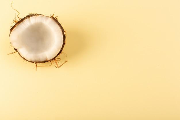 Вид сверху кокосовых орехов нарезанный молочно-свежей спелой, изолированный на кремовом цвете
